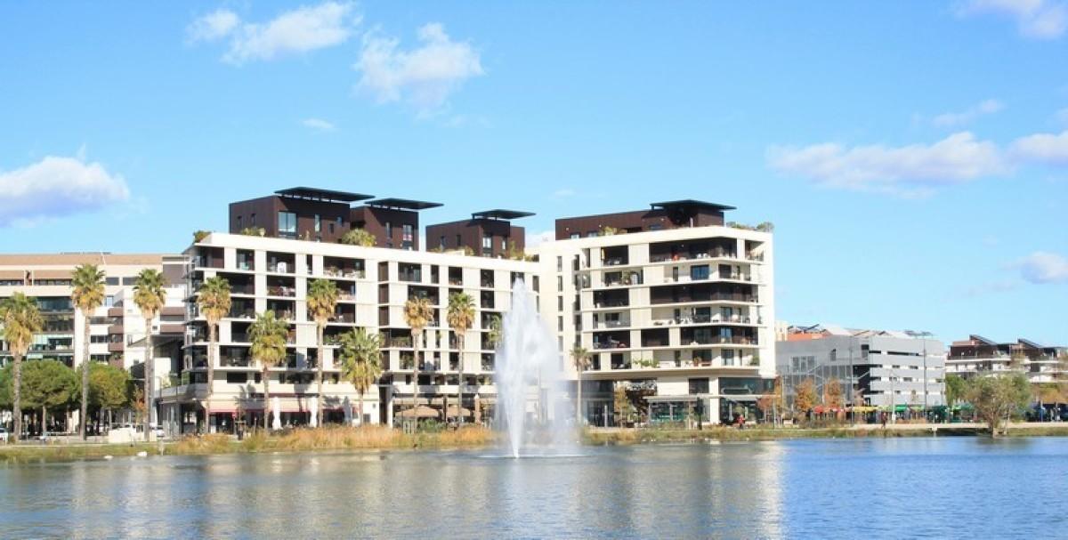 Un immeuble donnant sur un lac artificiel