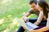 Couple qui se renseigne sur internet dans un parc.