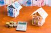 Financer projet immobilier Montpellier – Maison fait avec des billets de banque à côté d'une calculatrice et de pièces de monnaie