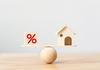 Projet immobilier à Montpellier – Cube pourcentage et maison en équilibre sur une planche posée sur une boule en bois.