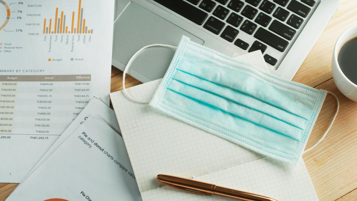 Immobilier à Montpellier – Masque chirurgical posé sur un ordinateur, un cahier et des documents.
