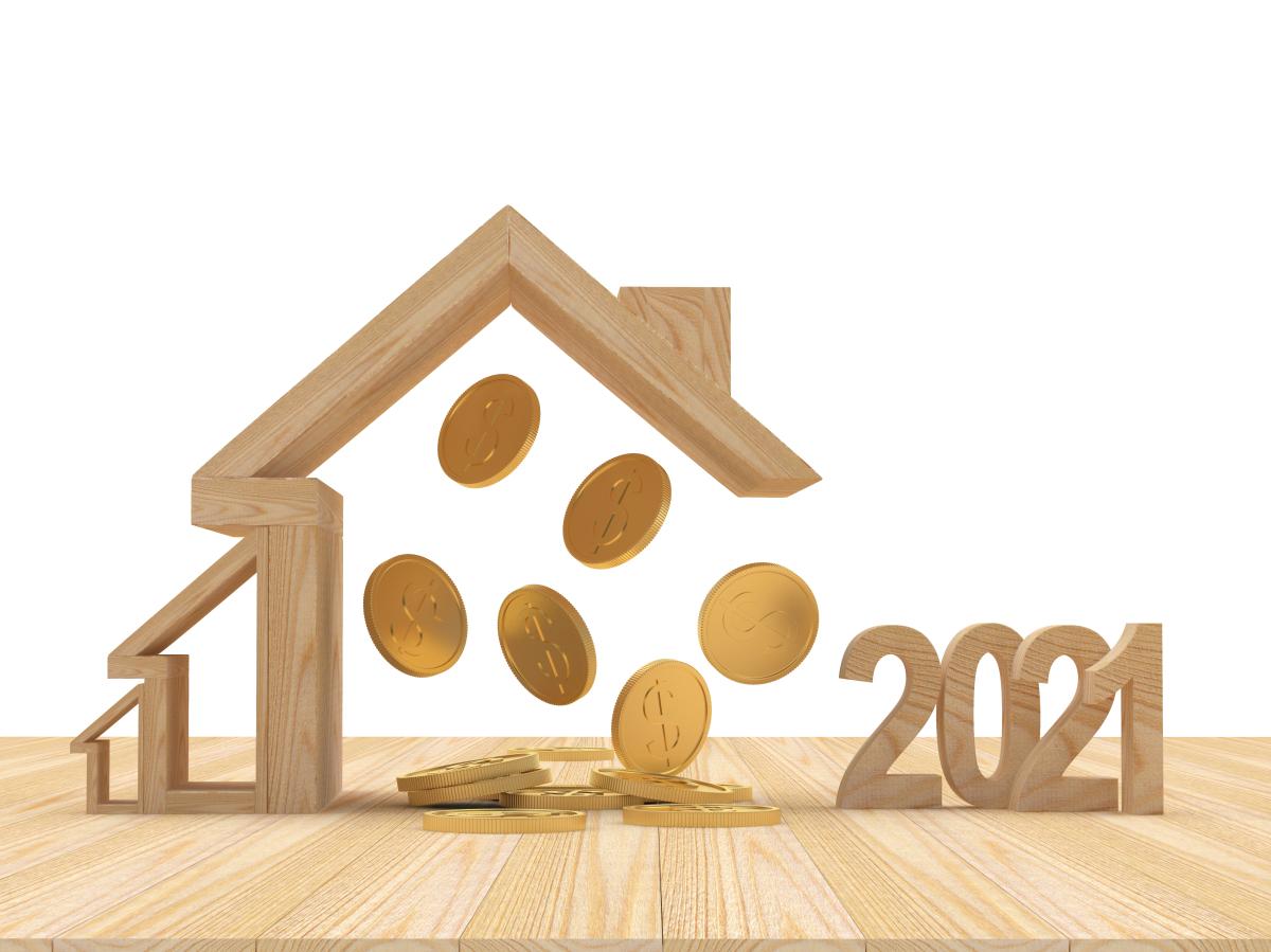 Investir dans l'immobilier à Montpellier en 2021 – Maisons en bois avec des pièces de monnaie qui tombent et les chiffres 2021 en bois.