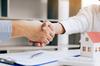 Investir dans l'immobilier à Montpellier – Dans une agence, deux personnes qui se serrent la main à proximité d'un contrat et d'une figurine de maison