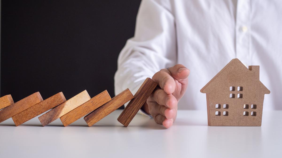 conseil achat immobilier neuf – Une main protégeant une maison en bois