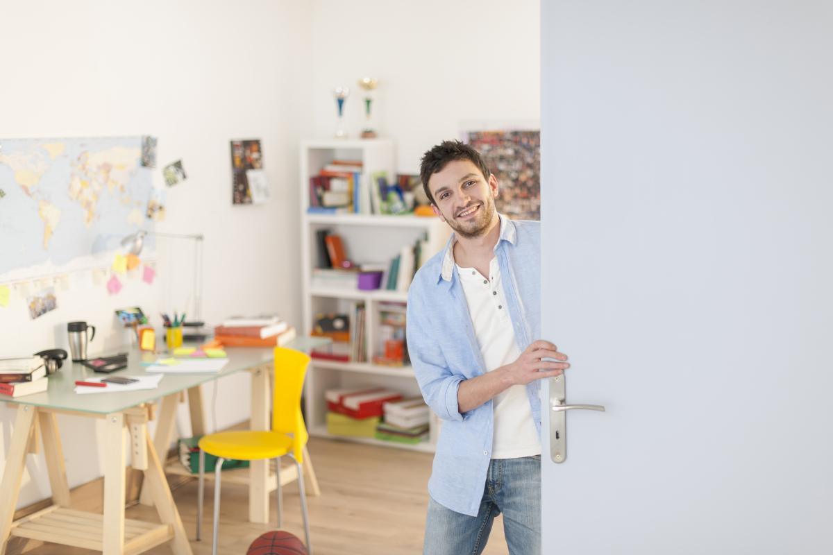 Jeune homme dans son appartement étudiant