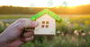 Maison en bois de la taille d'une main représentant l'immobilier écologique
