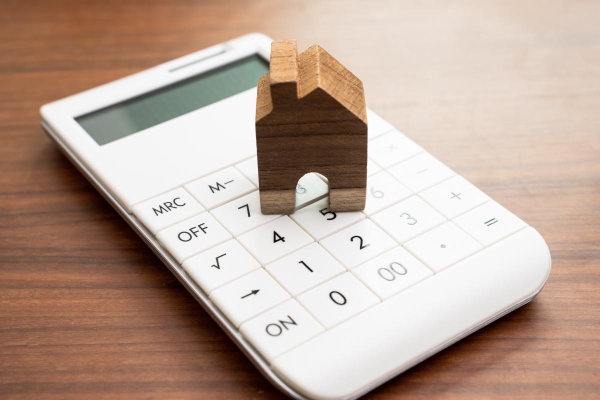 Calculatrice blanche avec une petite maison en bois posée au dessus
