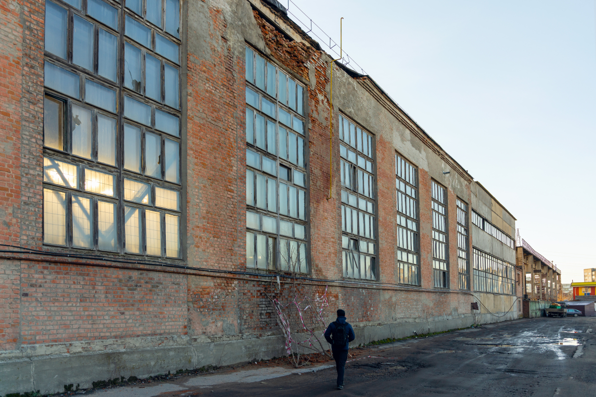 Loi 4D – Homme marchant devant un bâtiment désafecté