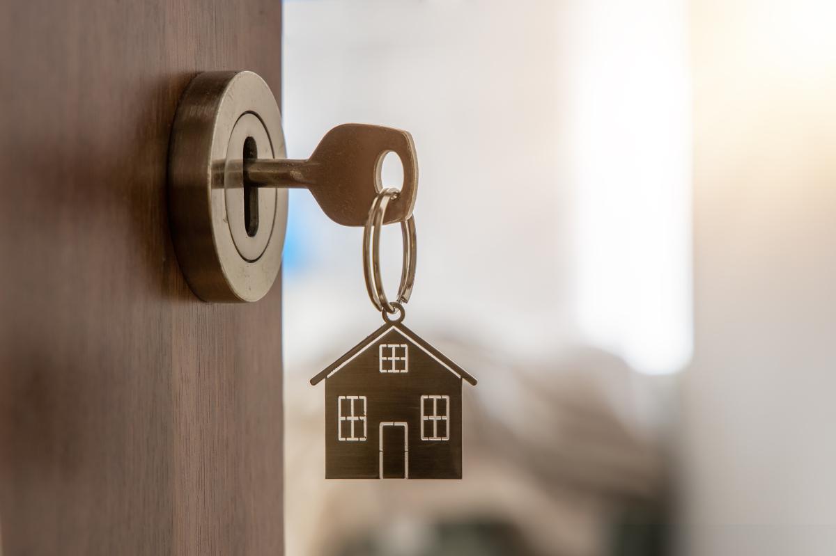 Louer un appartement à Montpellier - Clés avec un porte clé en frome de maison sur une porte ouverte