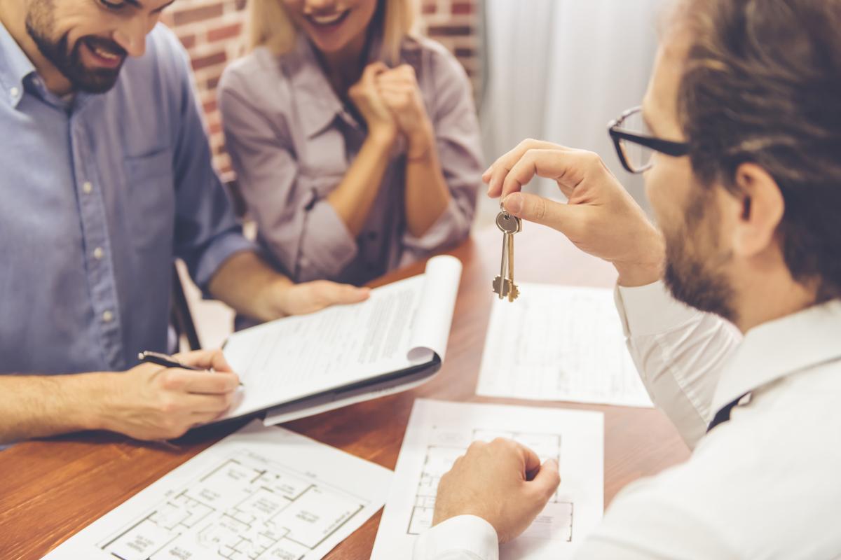 Louer un appartement à Montpellier - Agent immobilier remettant les clés d'un appartement à un couple qui signe un contrat